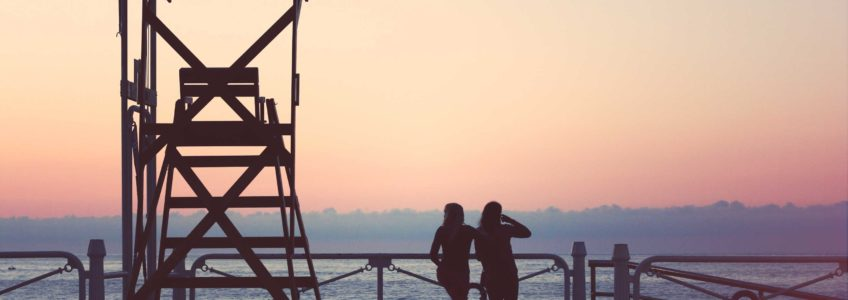 Two people standing in the sunset by the coast guard tower.